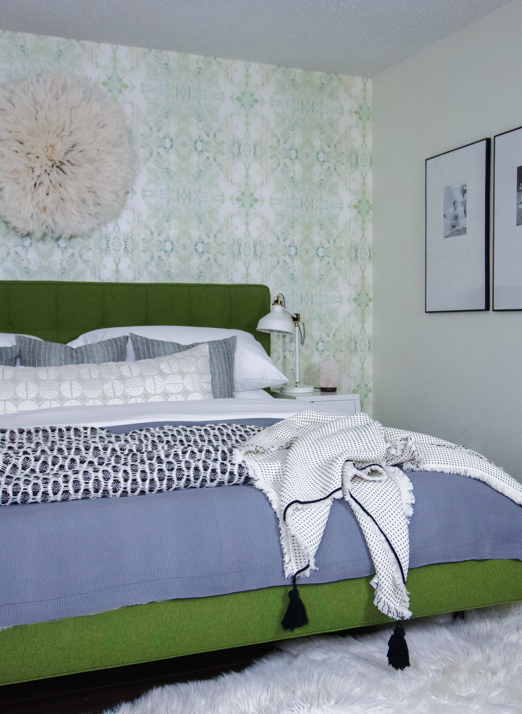 A beautiful bedroom with green flowered wallpaper and photos on the wall, and a throw blanket on the edge of the bed