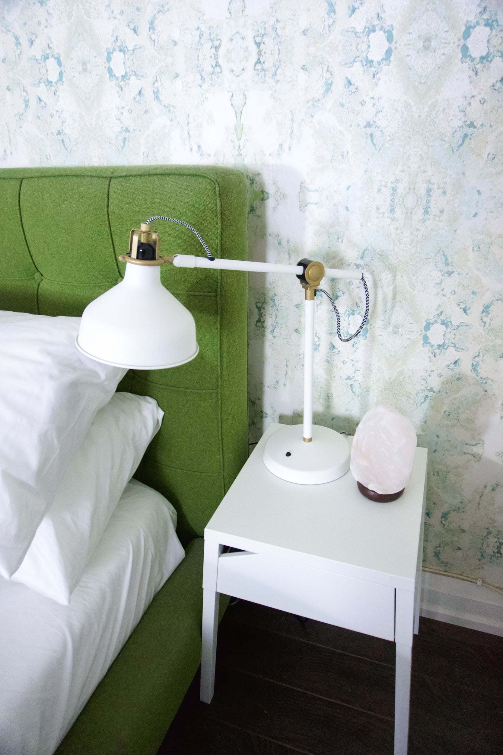 A beautiful bedside table and white lamp adjacent to a salt lamp