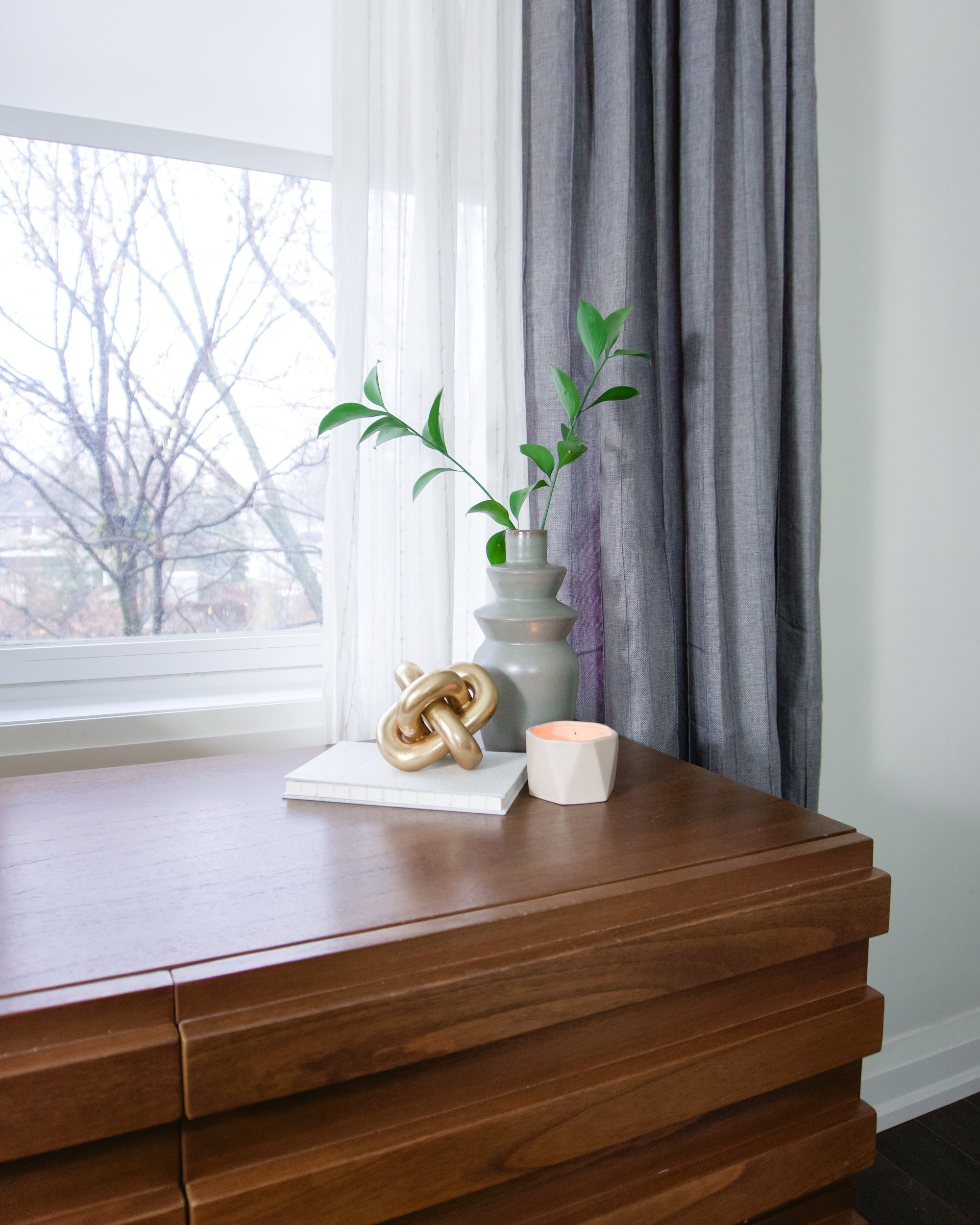 A cute plant in eccentric grey vase nested on a wooden dresser by the window