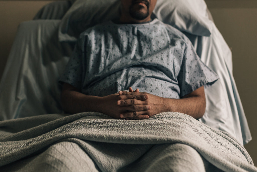 a man propped up in hospital bed sick needs sleep