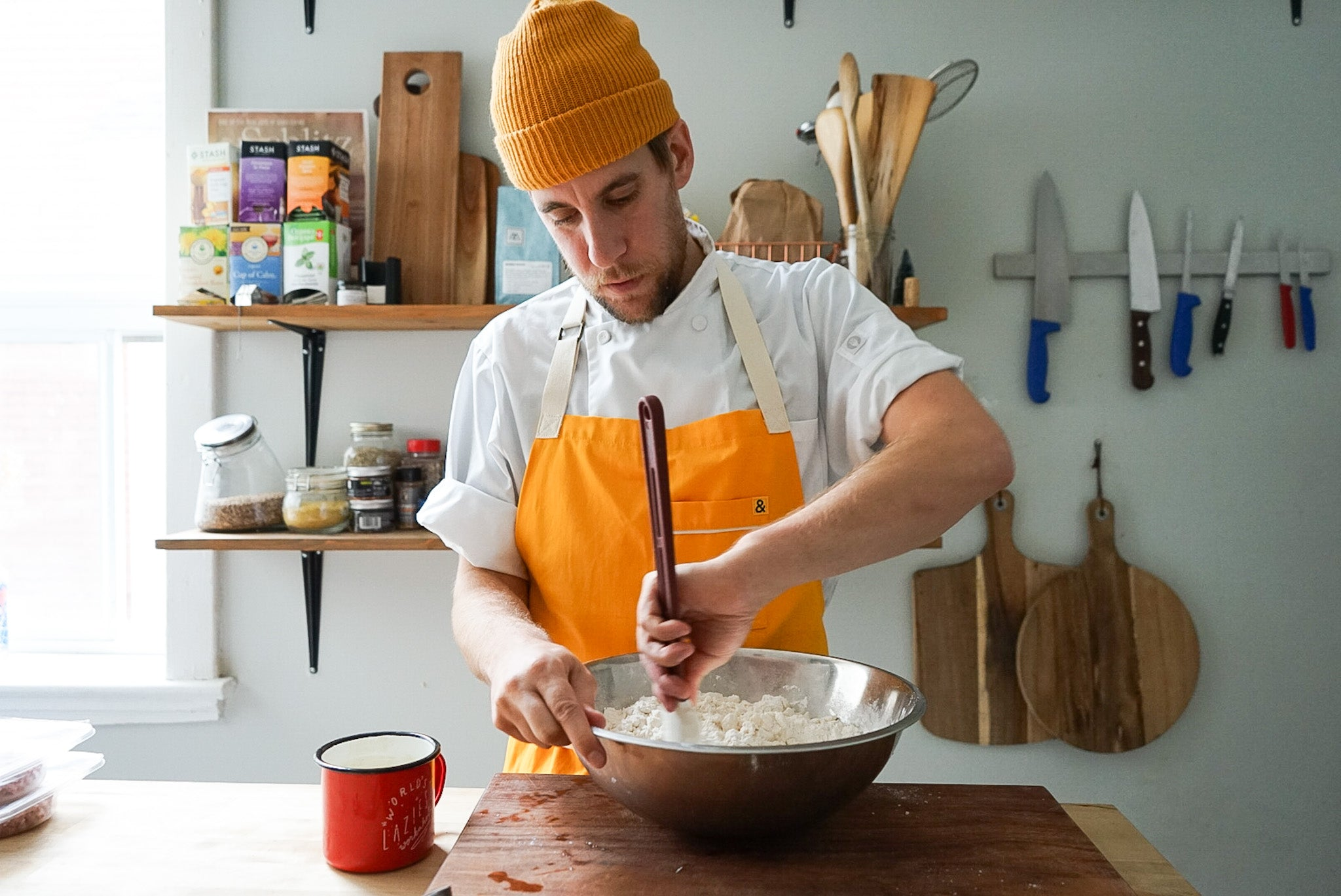 Fraser Fitzgerald mixing the ingredients of the tourtiere pie crust wearing orange in his kitchen
