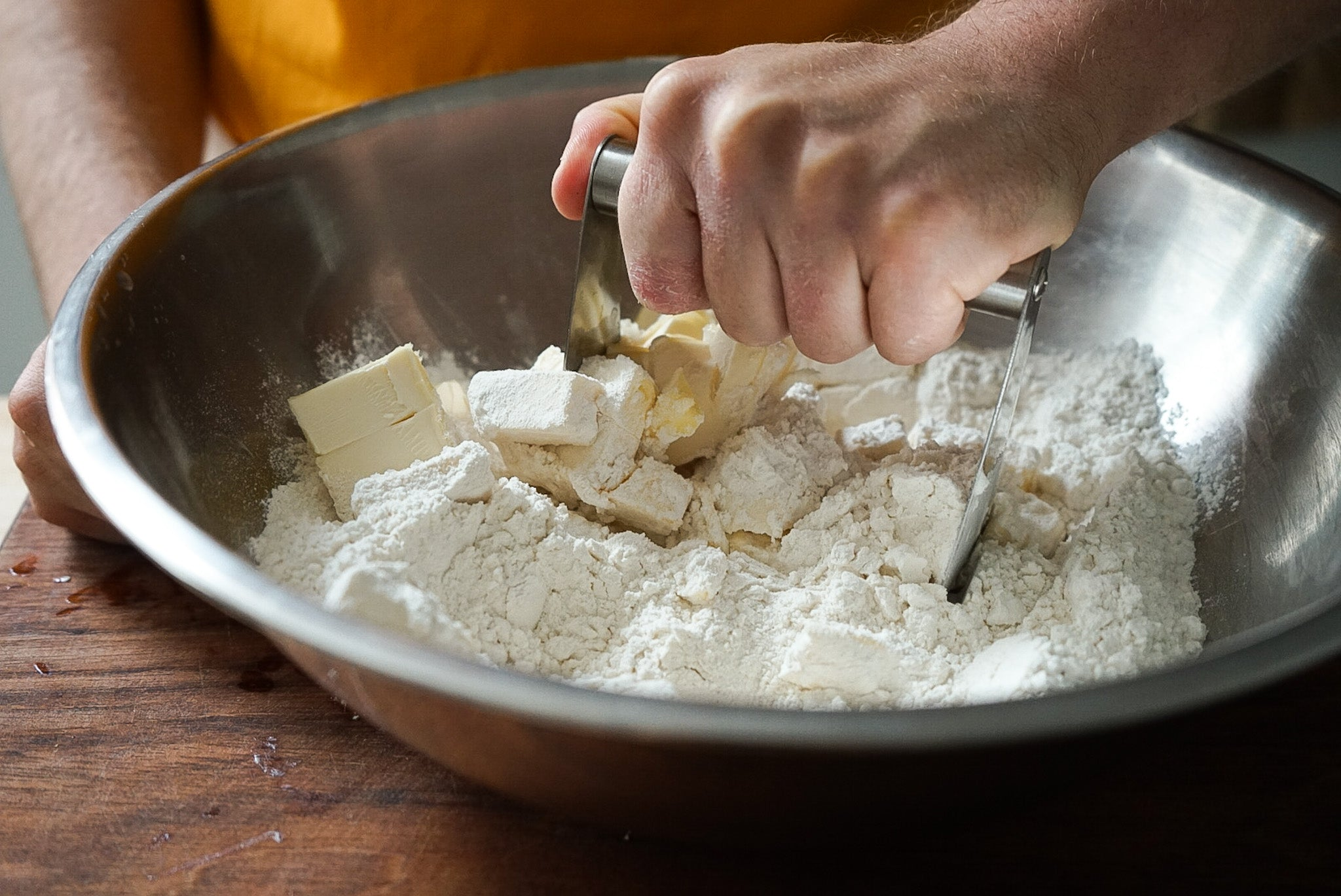 hand mixing bowl crushing butter sticks with flour for pie dough