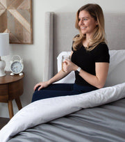 Women sitting up in bed with a cup of coffee and haven sleep company bedface sateen collection in white and grey