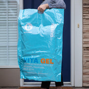 Woman carrying a Blu Sleep Bedface VitaGel 4 in 1 pillow bag with Blu Sleep logo. It says Queen down the side and Vita Gel across front with details of the Pillow on bag