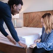 man and woman covering the edge of a Bedface Silver Mattress protector over the corner of Haven Mattress