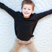 "Smiling little boy wearing a black sweater and beige pants doing a snow angel position across a 6"" Haven Jr mattress"