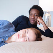 man staring lovingly at woman as she sleeps on a Bedface icegel pillow on a Haven Mattress