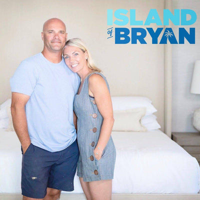 Sarah and Bryan Baeulmer of Island of Bryan HGTV show standing in fron tof a Haven bed-in-box mattress with white bedface sheets and white duvet cover with show logo in top right corner