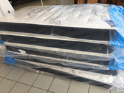 multiple brand new twin sized Haven Mattresses stacked up ready for donation