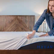 Woman pulling back a Bedface Silver Mattress protector of the corner of a Haven Mattress to show the Haven Mattress Blue logo at end of bed