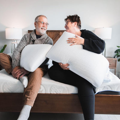 Man and woman both holding Bedface VitaGel 4 in 1 pillows looking at each other smiling while sitting on top of a Haven Mattress