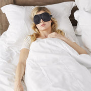 Woman in white sleeping with a pair of Bedface Blacjout 40 blinks sleep mask in black on memory foam pillow and Haven mattress in Starlight white sheet set with a white duvet cover pulled up to cover her