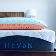 uncased Bedface VitaGel 4 in 1 pillow laying on top of an embossed Haven Mattress with Haven embroidered in Light blue at the foot of mattress