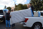 Three Haven Mattress staff loading bed-in-box mattresses into back of truck for donation to those in need