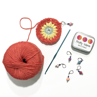 Crocheted centre for Sunburst Granny Square with crochet hook and Pretty Warm Designs crochet stitch markers