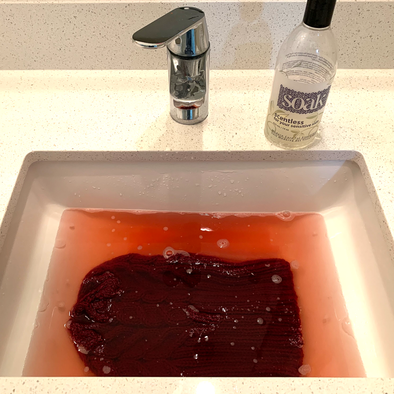 Sink full of water tinged with red dye from a knitted hat and a bottle of Scentless Soak