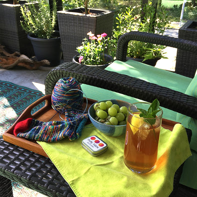 Outdoor patio with iced tea, grapes, chair and planters, sock knitting by Pretty Warm Designs