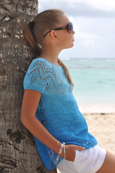 Saona knitted sweater pattern by designer Natalie Pelykh on young girl leaning against a tree at the beach