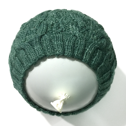 Green knitted lace hat pulled over a round balloon