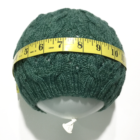 Green knitted hat pulled over a round balloon with measuring tape around the circumference