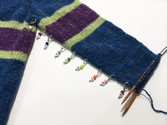 Locking stitch markers used to mark decrease rows on a knitted sweater sleeve