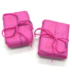 Tins wrapped in pink tissue paper with yarn bows