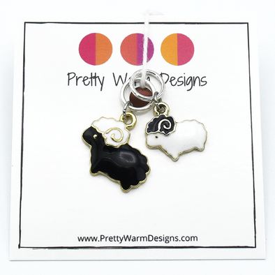 Package of two knitting stitch markers containing one black sheep and one white sheep ring marker attached to white cardstock with Pretty Warm Designs logo and text