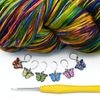 Set of six enamel butterfly charm crochet locking stitch markers in red, yellow, green, blue, pink and purple with brightly coloured variegated yarn and yellow handled crochet hook for crochet by Pretty Warm Designs