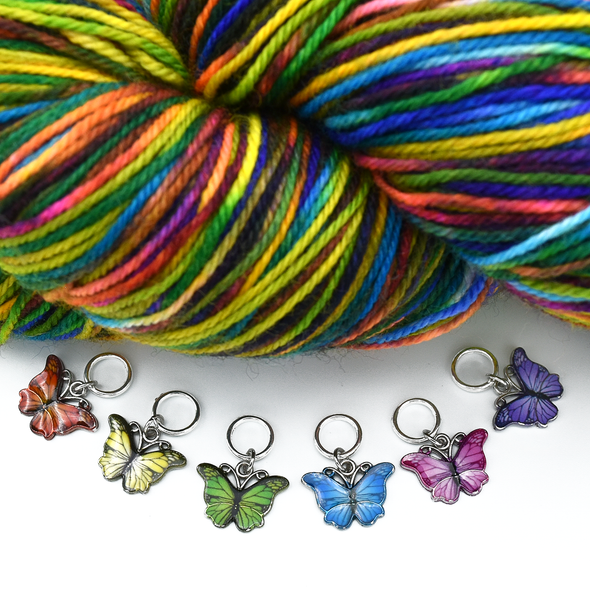 Set of six enamel butterfly charm snag free ring stitch markers in red, yellow, green, blue, pink and purple with skein of colourful variegated yarn for knitting by Pretty Warm Designs