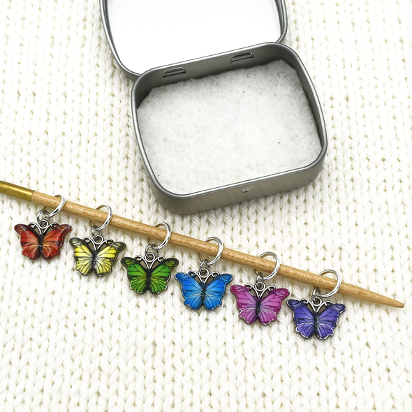 Set of six enamel butterfly charm snag free ring stitch markers in red, yellow, green, blue, pink and purple on knitting needle resting on white knitted square with storage tin for knitting by Pretty Warm Designs