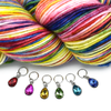 Set of six coloured rhinestones in red, pink, amber, green, turquoise and blue set in silver toned snag free ring stitch markers for knitting by Pretty Warm Designs and a variegated pink, blue, yellow, green, red and purple skein of yarn