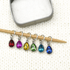 Set of six coloured rhinestones in red, pink, amber, green, turquoise and blue set in silver toned snag free ring stitch markers on a knitting needle and open decorative tin by Pretty Warm Designs