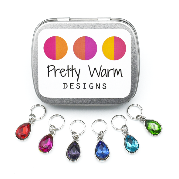 Set of six coloured rhinestones in red, pink, purple, blue, turquoise and green set in silver toned snag free ring stitch markers for knitting and decorative tin with Pretty Warm Designs text and logo