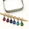 Set of six coloured rhinestones in red, pink, purple, blue, turquoise and green set in silver toned snag free ring stitch markers on a knitting needle and open decorative tin by Pretty Warm Designs