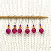 Set of six fuchsia pink glass crackle beads, orange Austrian crystals, purple seed beads and nylon coated snag free wire stitch markers on needle for knitting by Pretty Warm Designs