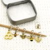 Set of six gold toned bee themed charms snag free ring stitch markers on needles with tin for knitting by Pretty Warm Designs