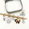 Set of six knitting themed charms snag free ring stitch markers with tin on knitting needle and white knitted background by Pretty Warm Designs