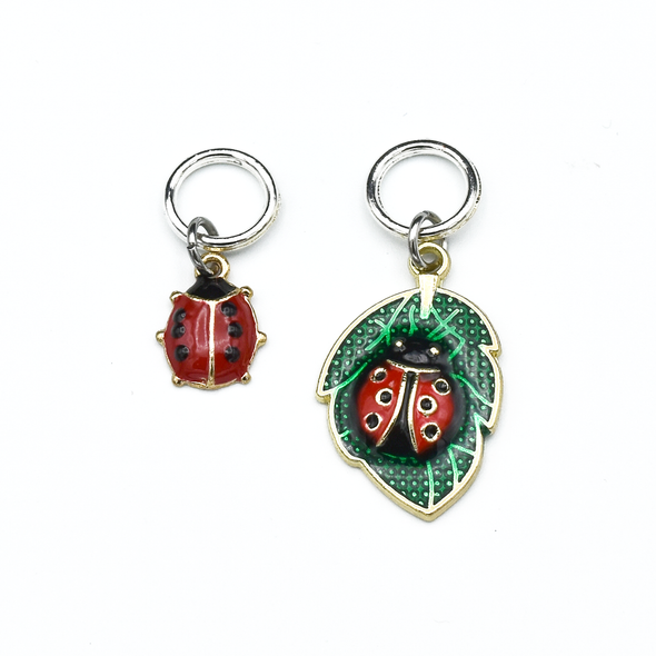 One red and black ladybug and one red and black ladybug on a green leaf enamel charms ring knitting stitch markers by Pretty Warm Designs