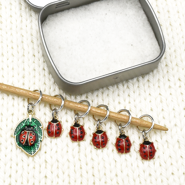 Set of five red and black enamel ladybug and one red, black and green ladybug on a leaf charms snag free ring stitch markers on knitting needle with open tin for knitting by Pretty Warm Designs