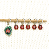 Set of five red and black enamel ladybug and one red, black and green ladybug on a leaf charms snag free ring stitch markers on a knitting needle resting on a white piece of knitting by Pretty Warm Designs