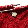 Enamel white and black sheep charm snag free ring stitch marker on knitting needles with red cabled yarn swatch by Pretty Warm Designs