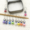 Set of ten different colours of striped glass beads, blue seed beads, antiqued silver alloy heart beads and snag free wire stitch markers on needle with tin for knitting by Pretty Warm Designs
