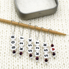 Set of six acrylic beads with BOR, K2T, SSK and red heart, deep purple Austrian crystal beads and wire snag free stitch markers on needle with tin for sweater knitting by Pretty Warm Designs