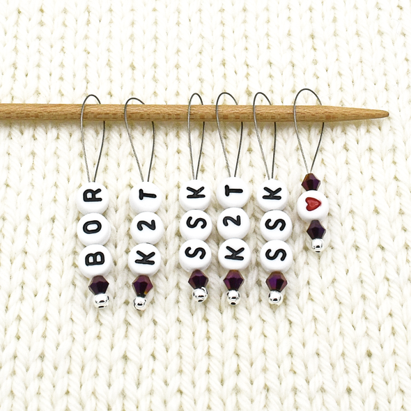 Set of six acrylic beads with BOR, K2T, SSK and red heart, deep purple Austrian crystal beads and wire snag free stitch markers on needle for sweater knitting by Pretty Warm Designs