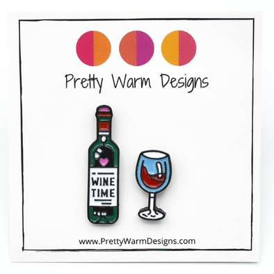 Set of two enamel pins, including bottle of wine enamel pin with Wine Time text on label and turquoise and red wine glass pin on white cardstock with Pretty Warm Designs text and logo