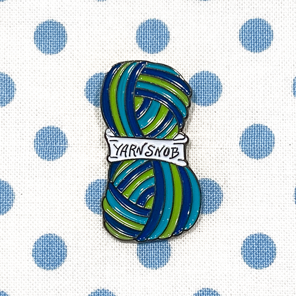 Blue, green and white enamel on silver metal Yarn Snob pin on a blue polka dot fabric project bag by Pretty Warm Designs