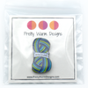 Packaged blue, green and white enamel on silver metal Yarn Snob pin for knitting and crochet project bags by Pretty Warm Designs