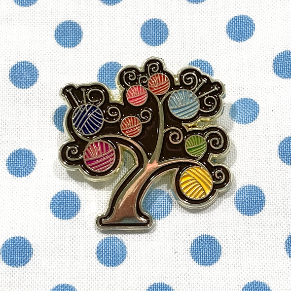 Multicoloured enamel on gold metal yarn tree pin on blue polka dot project bag by Pretty Warm Designs