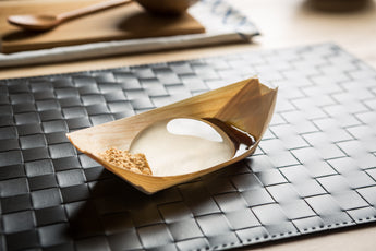 Raindrop Cake, clear jelly dessert on wooden boat. Asian dessert made of water and agar. Vegan and vegetarian.