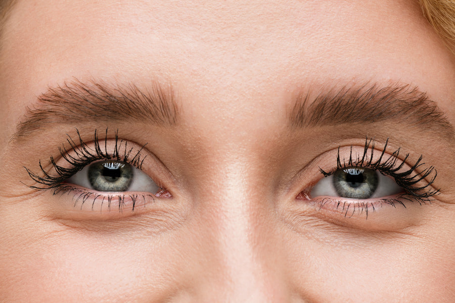 woman smiles after applying fiber lashes